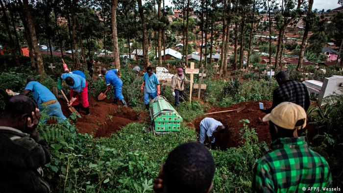 Uniformed workers burying the casket from an Ebola victim while people look on