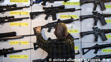 A man inspects a semi-automatic rifle at a gun fair in Lucerne, Switzerland