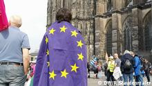 A person draped in the flag of the European Union stands in front of the Cologne Cathedral