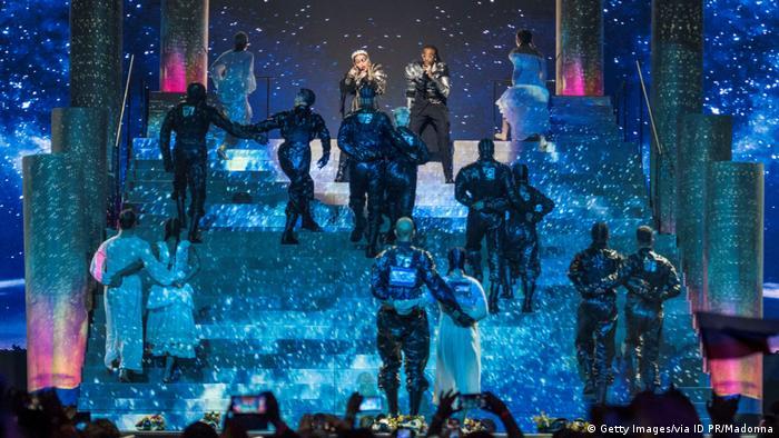 مدونا و گروهش در یوروویژن؛ یک رقصنده زن و یک رقصنده مرد پرچمهای فلسطین و اسرائیل بر پشت خود نصب کردهاند.