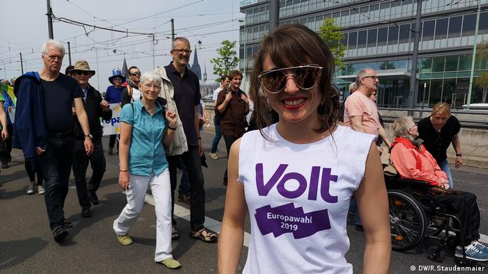 Lis Leifgen from the Volt party stands on the street with other participants in the background