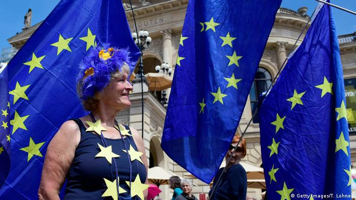 A participant in the One Europe for Everyone demonstration surrounded by blue EU flags in Frankfurt a. M. (Getty Images/T. Lohnes)
