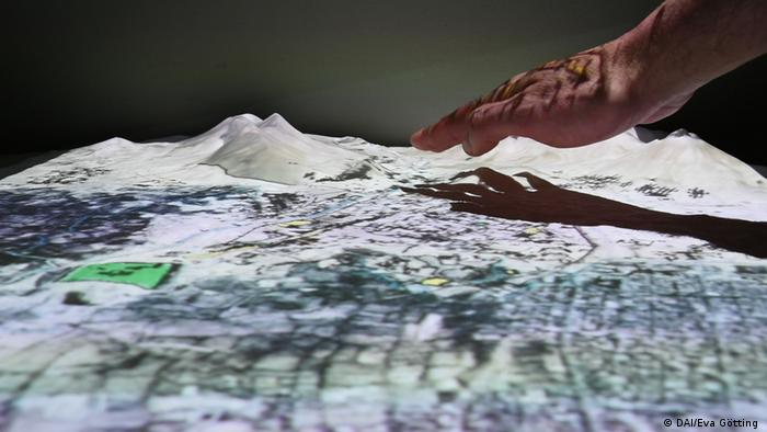 A hand reaches towards a 3D landscape model (DAI/Eva Götting )