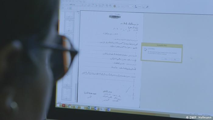 A woman looks at a computer screen with a document from the CIJA