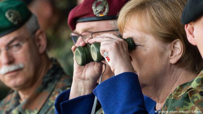 Merkel with military officers looking through binoculars