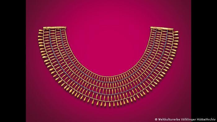 Goldener Halskragen vor rotem Hintergrund in der Ausstellung Pharaonen Gold – 3.000 Jahre altägyptische Hochkultur in der Völklinger Hütte. (Weltkulturerbe Völklinger Hütte/Archiv)