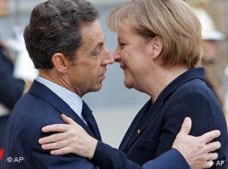 French President Nicolas Sarkozy and German Chancellor Angela Merkel greet one another