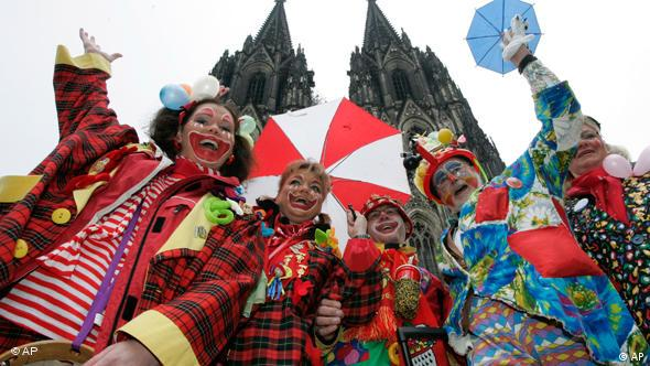 Clowns celebrating Carnival stand in front of the Cologne Cathedral