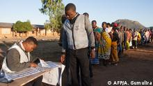 A polling officer watches as his colleague checks his details before he votes at Goliati Primary School in Goliati village, the home of Malawi's President Arthur Peter Mutharika in Thyolo District, southern Malawi, during presidential elections on May 21, 2019. - Malawi polls opened on May 21 after a closely-fought election campaign, with President Peter Mutharika battling to hold off two serious rivals in a race that has focused on corruption allegations and economic development. (Photo by AMOS GUMULIRA / AFP)