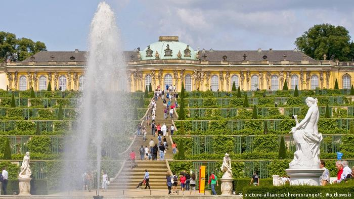 Fountain with Sanssouci Palace and gardens with sculptures behind it (picture-alliance/chromorange/C. Wojtkowski)