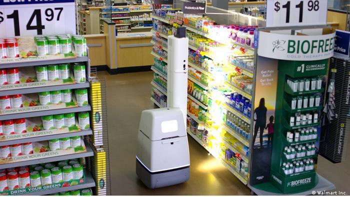 Prateleira de produtos do supermercado recebe feixe de luz de um robô que tem mais ou menos o tamanho da estante.