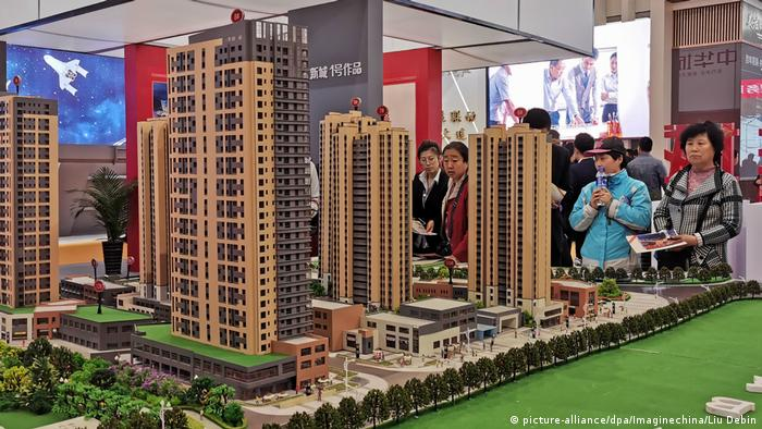 People stand next to a model of a proposed apartment block in Dalian city (picture-alliance/dpa/Imaginechina/Liu Debin)