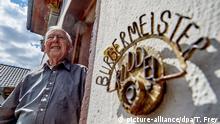 14.05.2019, Rheinland-Pfalz, Windhagen: Josef Rüddel, Bürgermeister von Windhagen, steht an der Tür seines Wohnhauses. Nach 56 Jahren als Bürgermeister stellt sich der 94-jährige nicht mehr der Wiederwahl. (Zu dpa: Deutschlands ältester Bürgermeister geht mit 94 in Ruhestand) Foto: Thomas Frey/dpa +++ dpa-Bildfunk +++   Verwendung weltweit