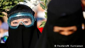 A woman wearing goggles protests the reelection of Indonesian President Joko Widodo