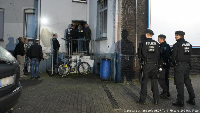 Police officers standing outside a building in North Rhine-Westphalia