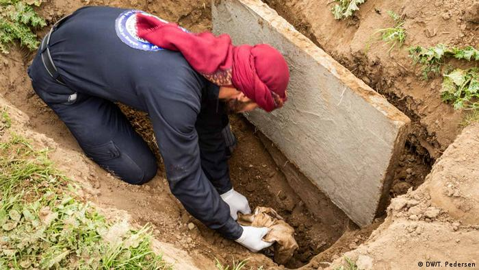 A man lifting a bundle from a grave