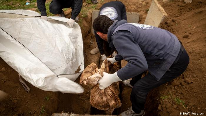 A man lifting a body bag out of a grave