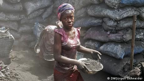 A woman holding a bowl of charcoal. Black sacks behind her
