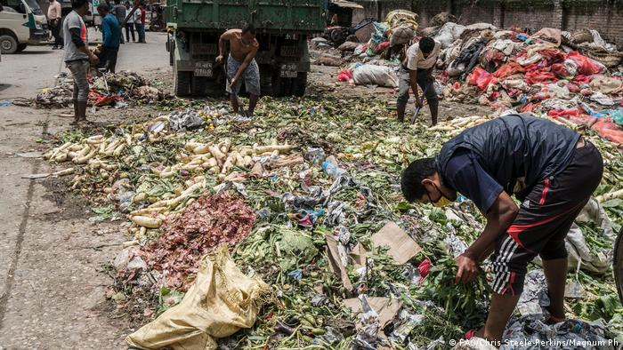 Workers in Nepal pile wasted food in a country seriously affected by climate change