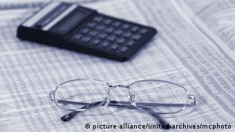 a calculator and a pair of glasses are placed on a newspaper page with market information