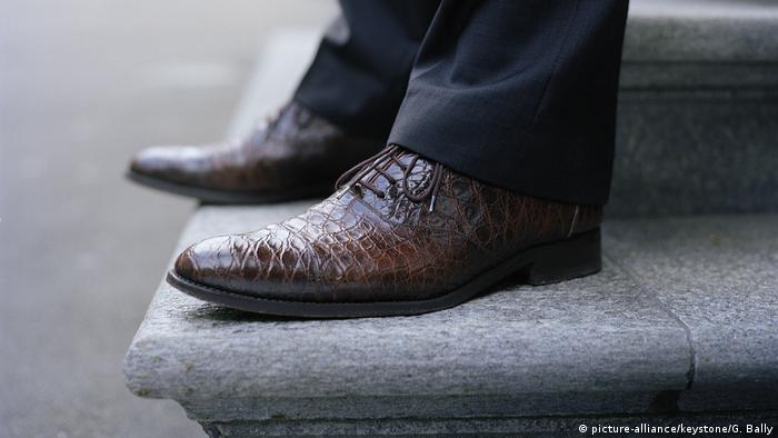 A close up of a man wearing crocodile skin shoes