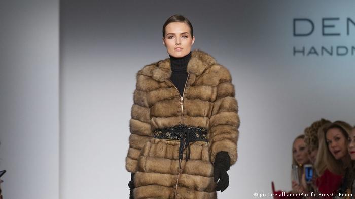 A woman walking down a runway wearing a belted fur coat