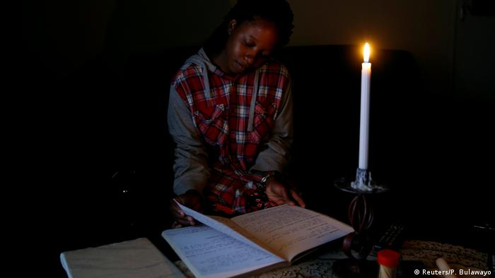 A women reads a book by candlelight