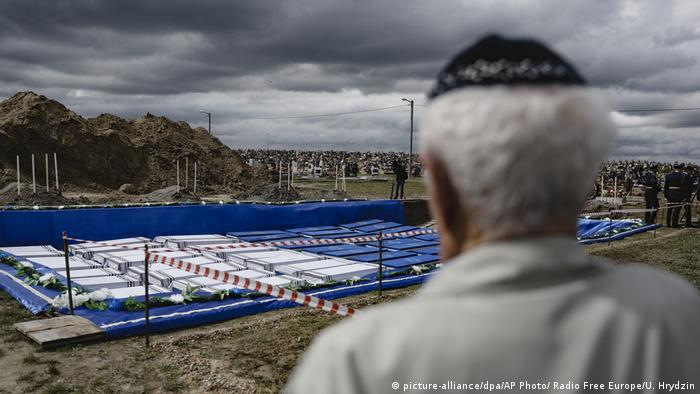 A man looks at coffins before burying the remains of Holocaust victims at a cemetery just outside Brest, Belarus (picture-alliance/dpa/AP Photo/ Radio Free Europe/U. Hrydzin)