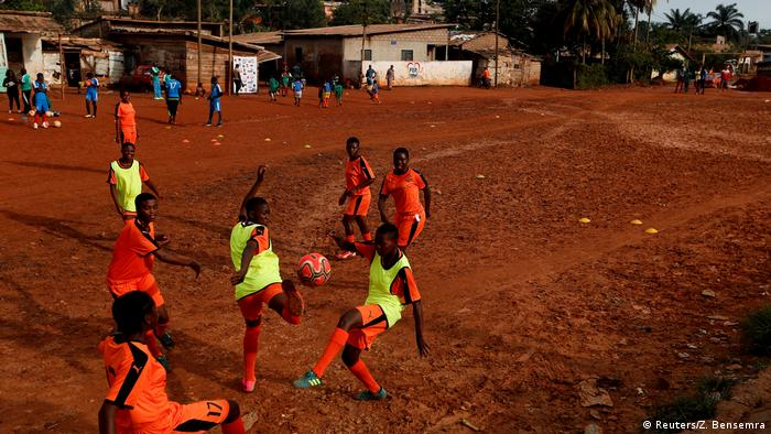 Girls playing football on a read earth football pitch (Reuters/Z. Bensemra)