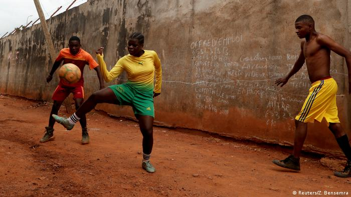 Gaelle Dule Asheri stops a ball while playing with young men on a street. Next to her - a wall with chalk writing on it keeps track of the score (Reuters/Z. Bensemra)