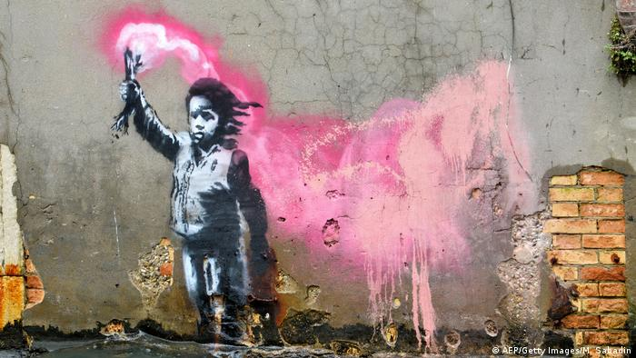artwork depicting a migrant child wearing a lifejacket holding a pink flare | Banksy | Schiffbrüchiges Kind (AFP/Getty Images/M. Sabadin)