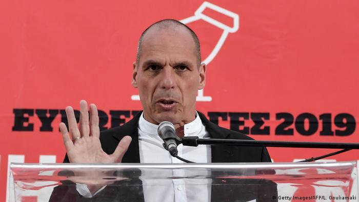 Yanis Varoufakis fala ao microfone, em uma bancada.