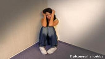 Frau in depressiver Haltung in einer Zimmerecke (Foto: picture alliance/dpa)
