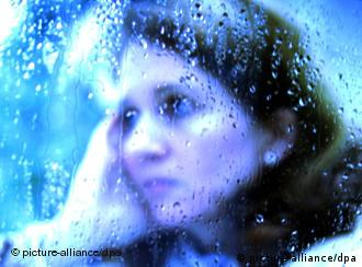 A depressed woman looks out of a rainy window