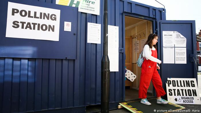 A woman walks out of a polling station in north London
