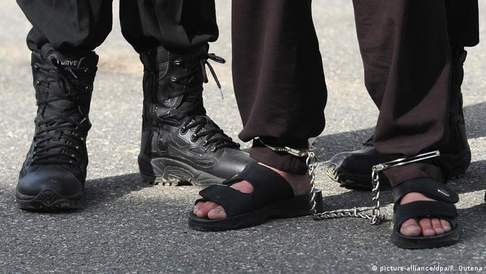 The feet of one of three men convicted of murder (right) and of an official (left) are seen