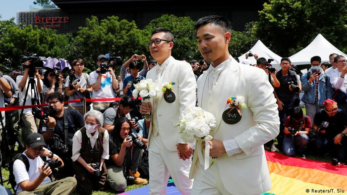 Gay newly-weds walk on a giant rainbow flag