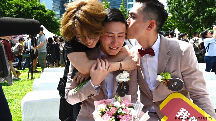Shane Lin is comforted by his partner Marc Yuan during a wedding ceremony