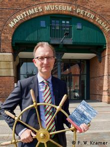 Erik Lindner vor dem Maritimen Museum in Hamburg, in der Hand das Steuerrad der SKYLUCK