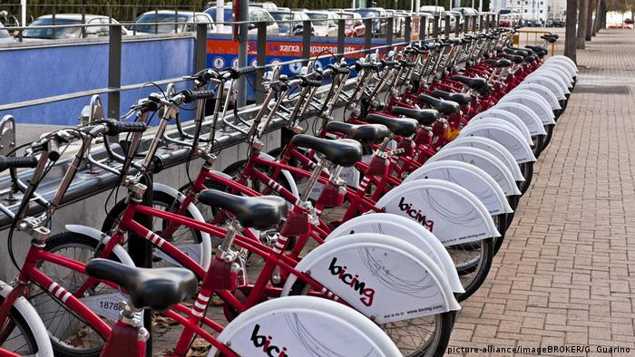 A bicycle hire center with red bikes parked in a row in Barcelona in Spain