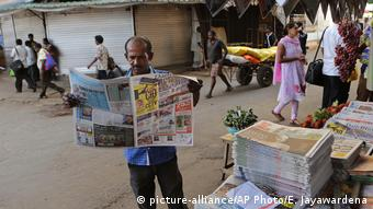 A man reads a newspaper at a newsstand in Colombo, Sri Lanka