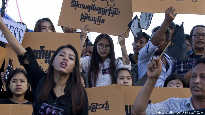 Protesters holding cardboard placards with slogans in Burmese