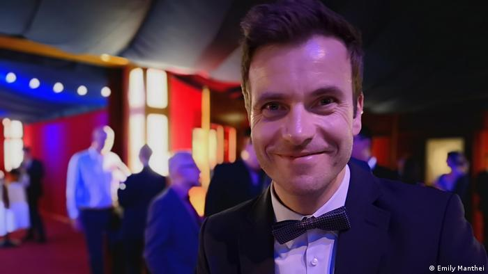 A man in a suite and bow ties smiles into the camera