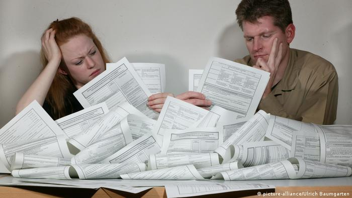 Two people frown while reading from a large pile of paper documents