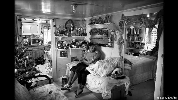 Fotoausstellung Lenny Kravitz - Drifter. Ein Paar kuschelt sich auf einem Sofa in einer weihnachtlich geschmückten Wohnung aneinander (Lenny Kravitz)