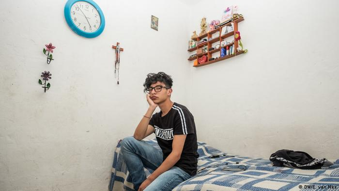 A boy sitting on his bed