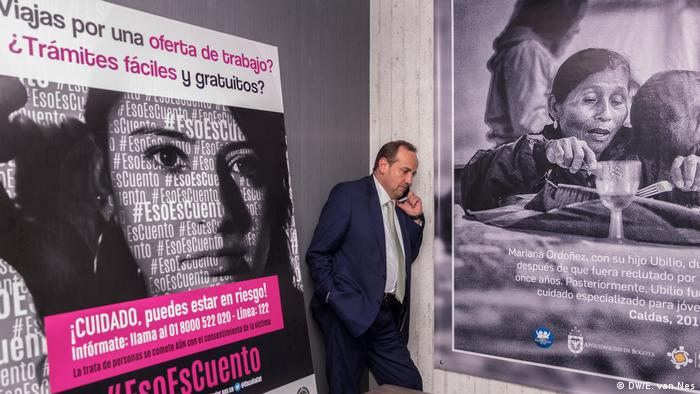 A man standing in front of two posters