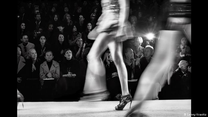 Fotoausstellung Lenny Kravitz - Drifter: Ein Model huscht auf dem Laufsteg vorbei, nur ein Bein und das Publikum dahinter sind scharf, der Rest verwischt (Lenny Kravitz)