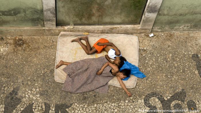 Crianças dormindo em um colchão na rua em Salvador
