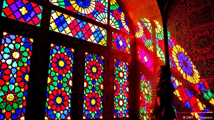 A tourist stands in the colored lights from the windows in the Mosque of Nasir-ol-Molk (DW/F. Schlagwein)